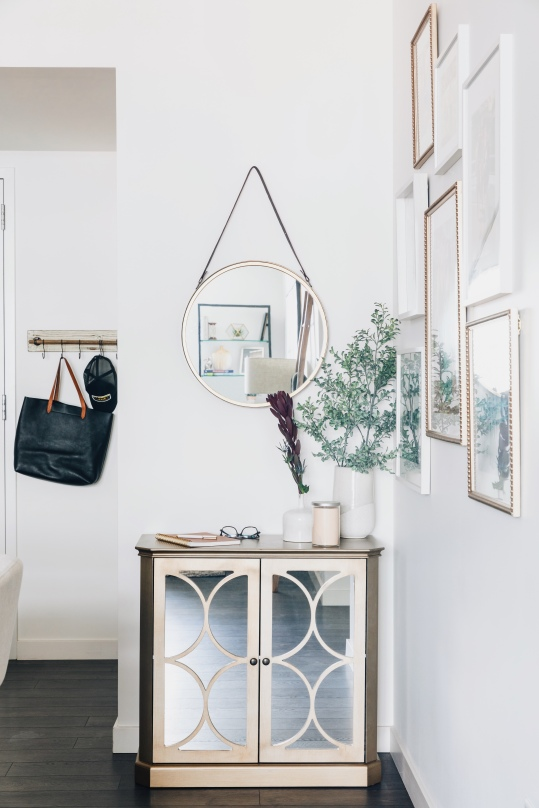 Mix white and metallic frames for a touch of glam in a modern gallery wall arrangement. Photo credit: Anna Hudson